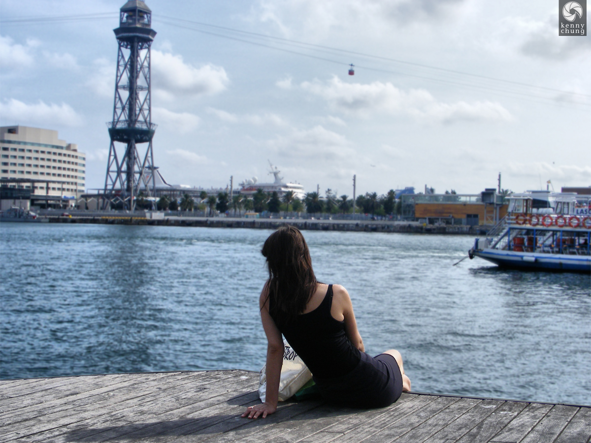 A girl sitting on the edge of Port Vell