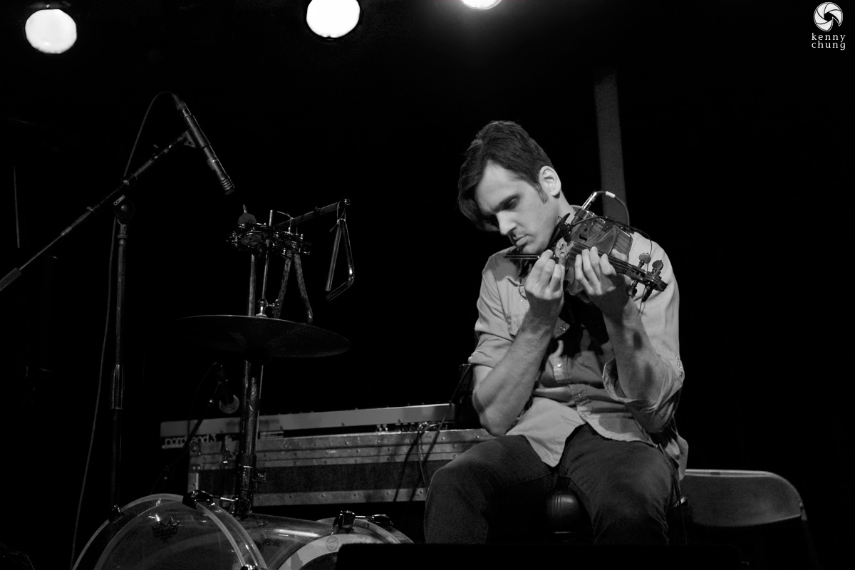Christopher Tignor playing violin with a tuning fork at Littlefield, Brooklyn