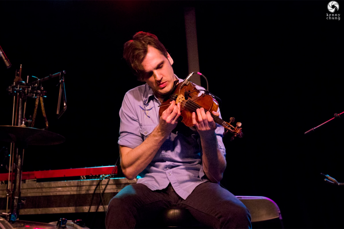 Christopher Tignor playing the violin with a tuning fork