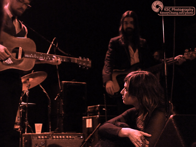 Nicole Atkins sitting on stage with The Black Sea