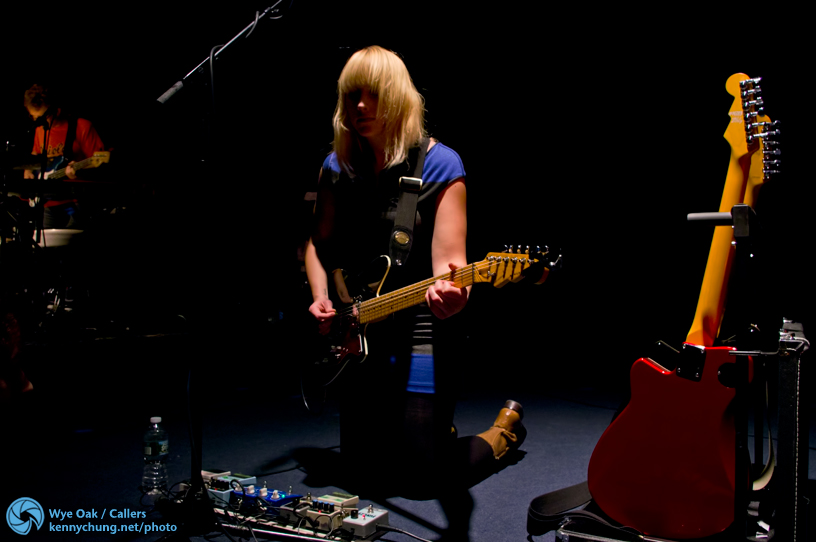 Jenn Wasner playing guitar on her knees in between songs, adjusting her pedals