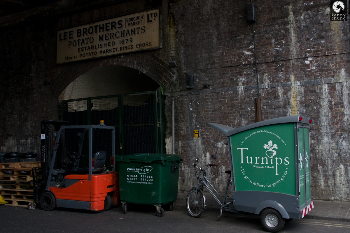 A sign for Lee Brothers Potato Merchants and a Turnips bicycle delivery wagon