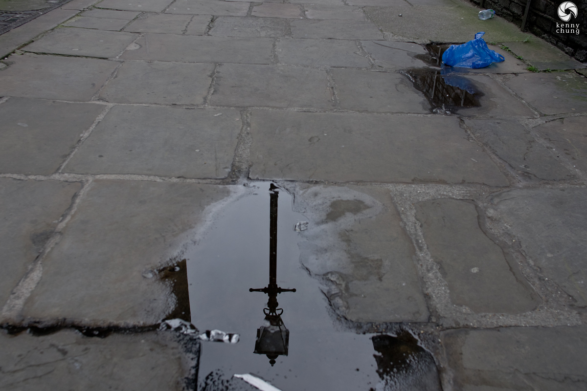 A streetlight reflected in a puddle in an alley in Shoreditch, London