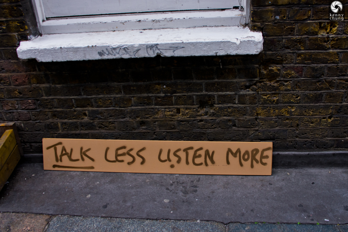 A spraypainted sign that said Talk Less, Listen More in an alley in Shoreditch, London