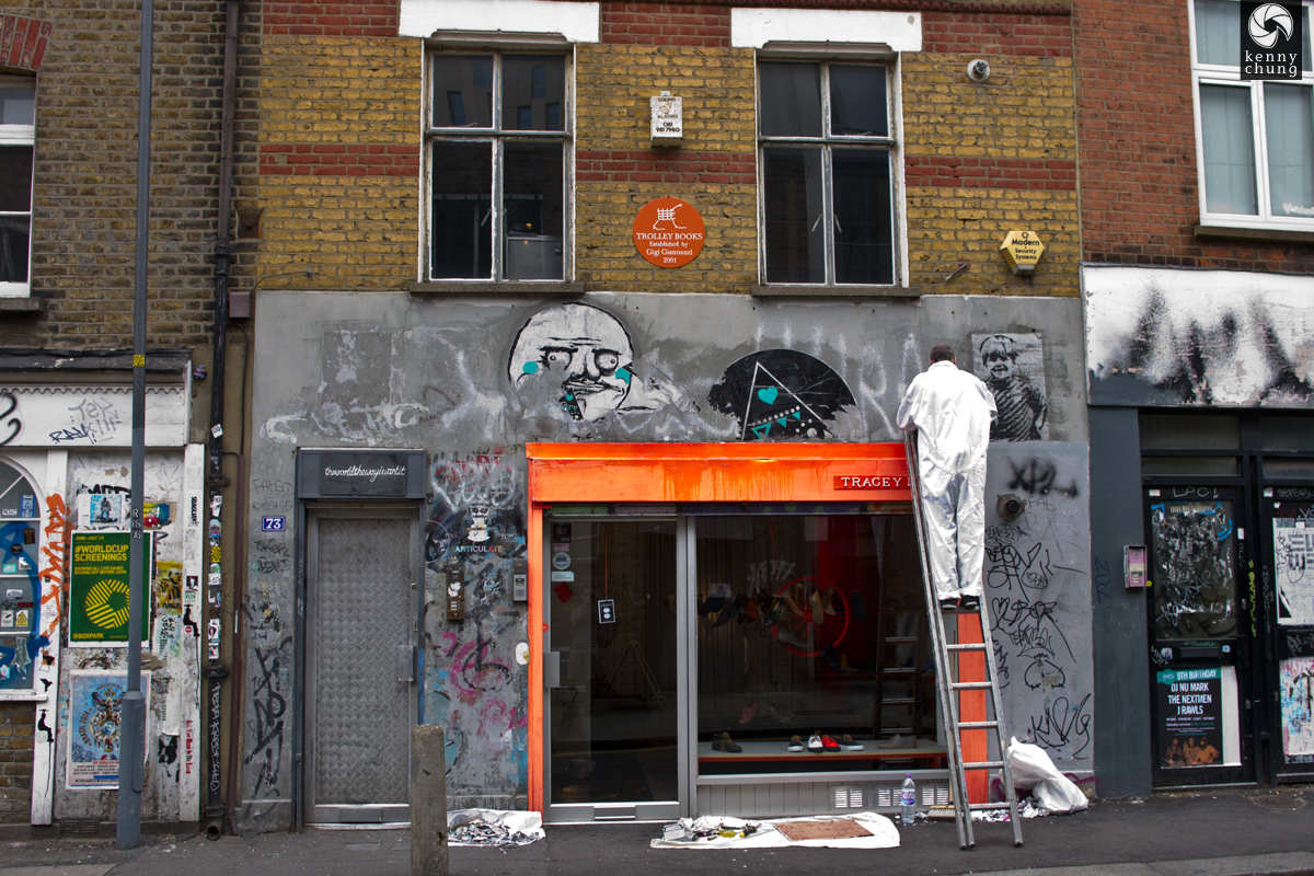 A painter cleaning up graffiti (including the Me Gusta meme) on a Shoreditch storefront