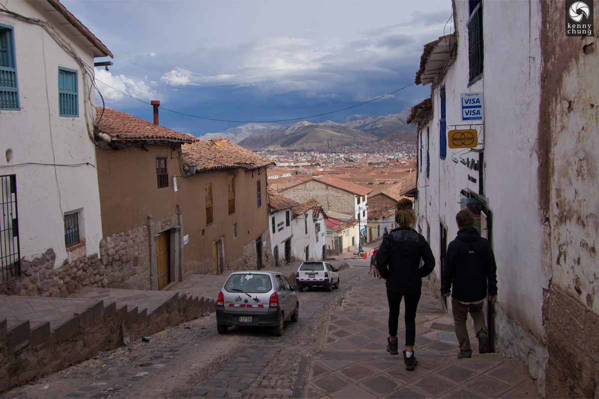 Steep streets in Cusco with mountains in the background