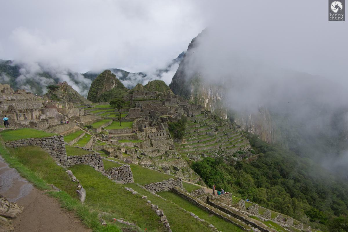 Machu Picchu ruins through the fog.
