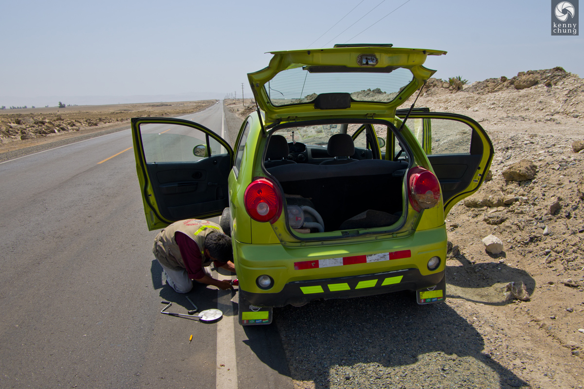 Changing a tire on the side of the road on the way to Paracas.