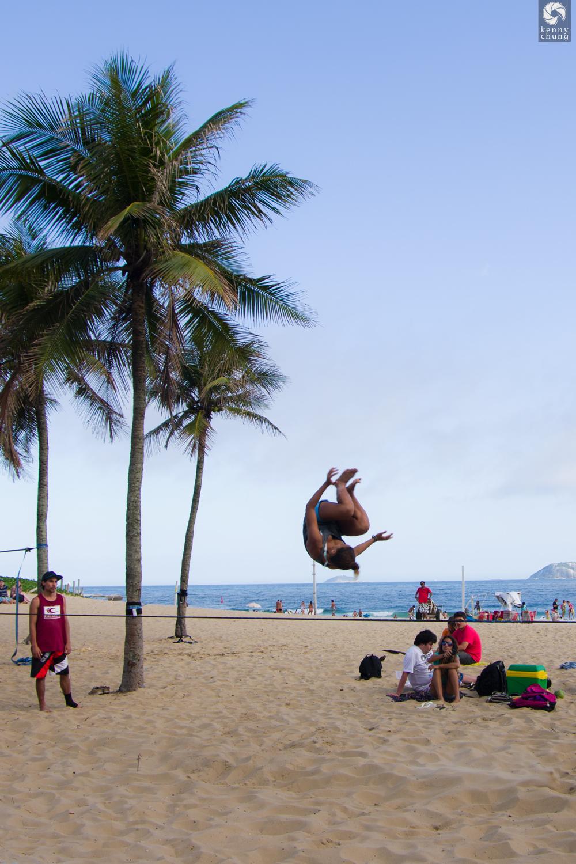Girl flipping on a slackline at Ipanema Beach, Rio de Janeiro
