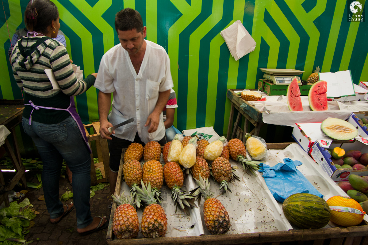 A street vendor cutting up pineapples at Ipanema Farmers Market in Rio de Janeiro