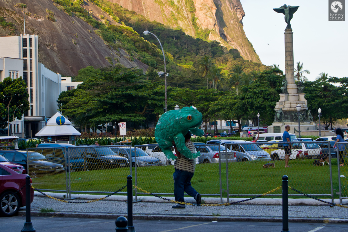 Man carrying a frog statue at Sugarloaf Mountain.