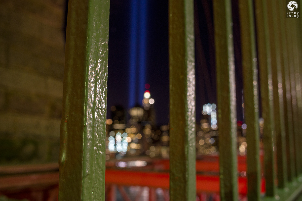 Tribute in Light through the Brooklyn Bridge fence
