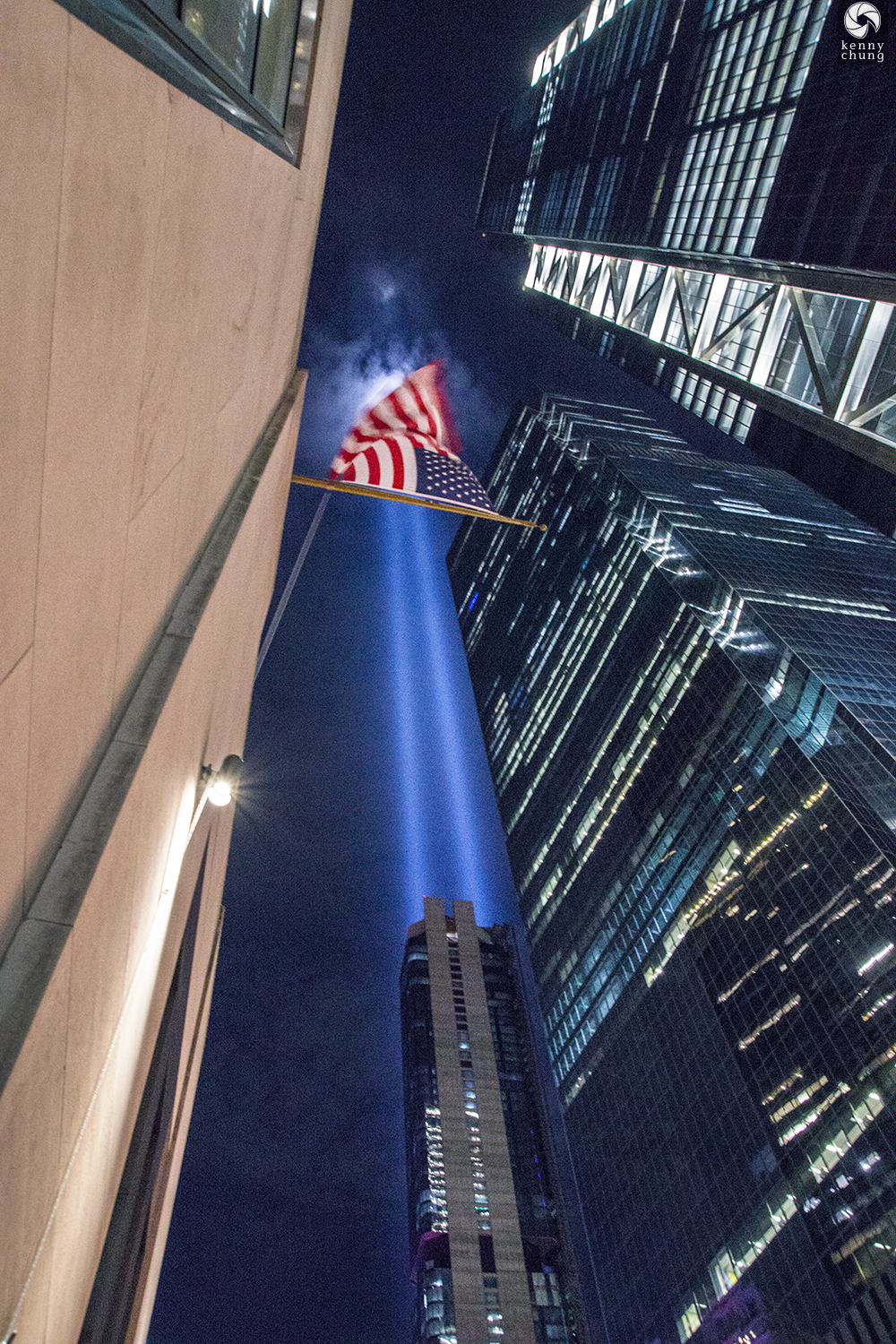 An American flag in front of the Tribute in Light