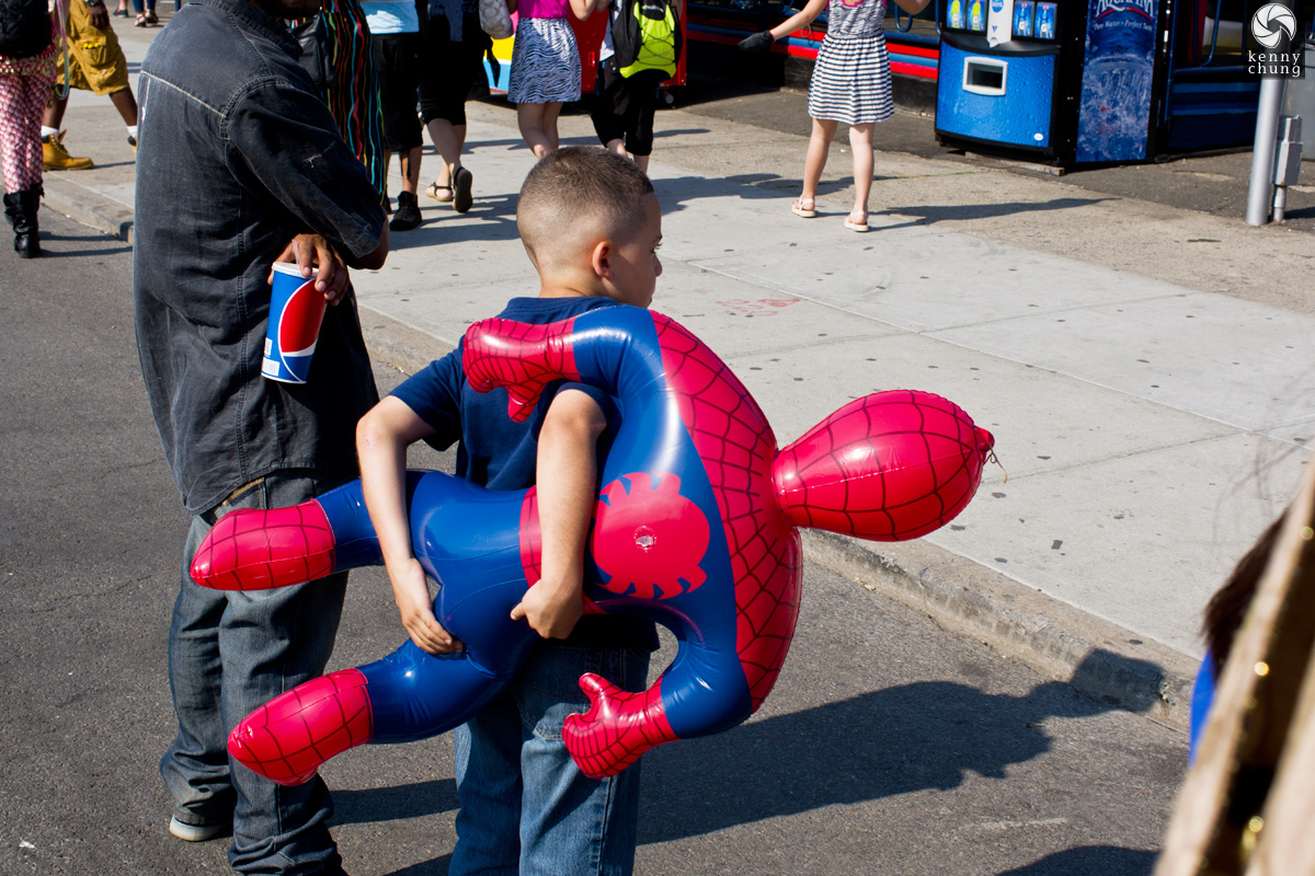 A boy holding his Spider-Man balloon prize at Coney Island